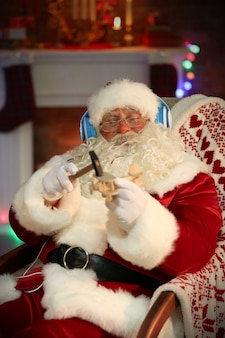 Санта-клаус сидит с наушниками, сидя в удобном кресле-качалке дома