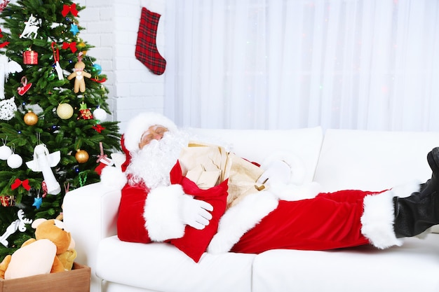 クリスマスツリーの近くで家で寝ているサンタクロース