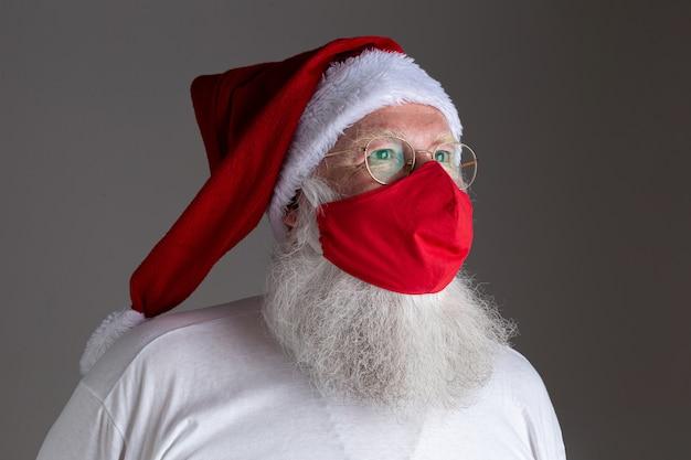 빨간 코비드-19 안전 마스크 뒤에 산타클로스가 웃고 있다. 사회적 거리두기가 있는 크리스마스.