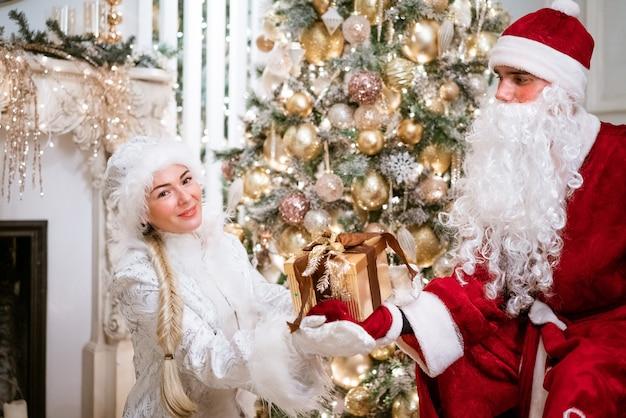 Santa claus and snegurochka posing by the new year tree