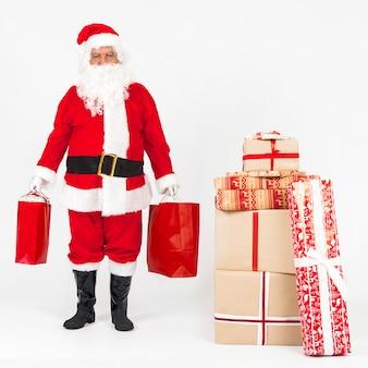 Санта-клаус стоит и приносит подарочные пакеты