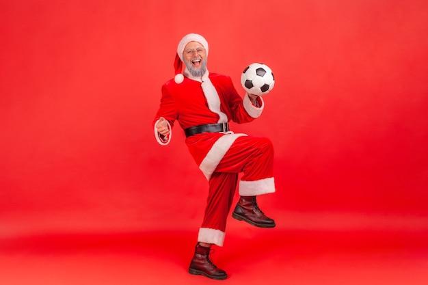 Санта-клаус стоит и играет с футбольным мячом, празднуя победу любимой команды.