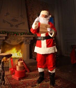 Санта-клаус стоит в своей комнате дома возле елки и большого мешка и читает рождественское письмо или список желаний.