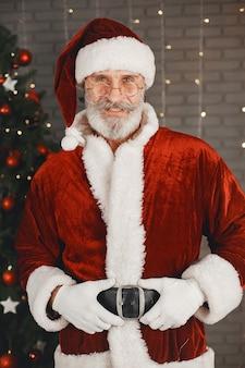Санта-клаус стоит у елки рождества. украшение дома.