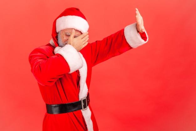 サンタクロースが立って、顔を覆い、手のジェスチャーを止めています。
