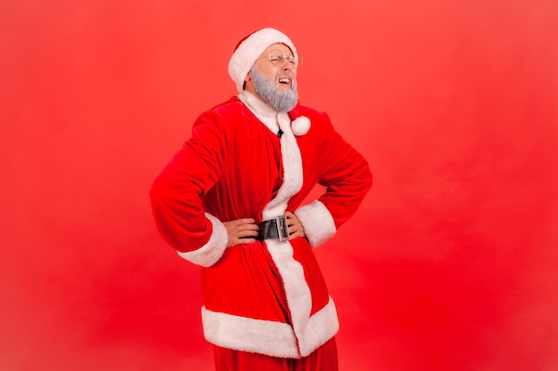 Santa claus standing and keeping hands on belly, suffering from pain, gastritis or constipation.