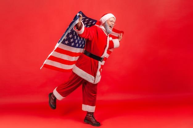 Санта-клаус стоит на одной ноге, делая вид, что летит с флагом сша в руках.