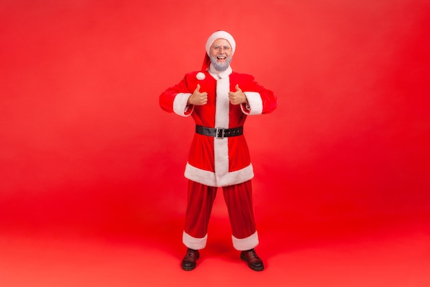 Santa claus standing and showing thumb up, approval hand sign, satisfied with result.
