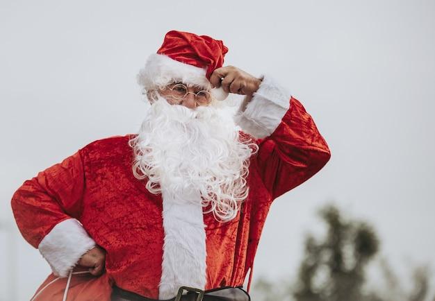 Санта-клаус стоит, положив руки на бедра, хватая его красную сумку. рождественское время