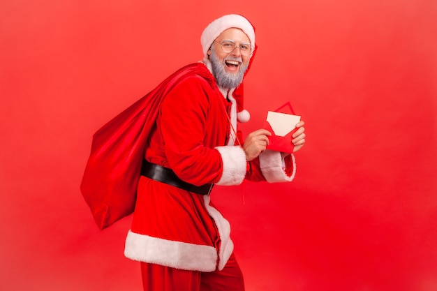 Santa claus standing with bag of presents and holding letter with christmas congratulations.