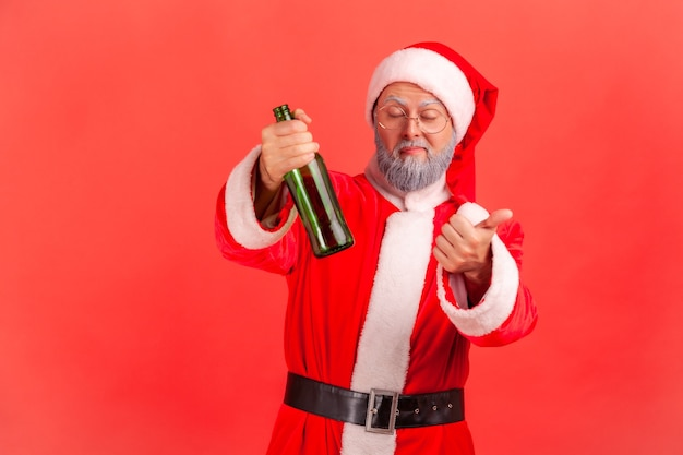 Santa claus standing with beer bottle, being drunk, standing with closed eyes and showing thumb up.