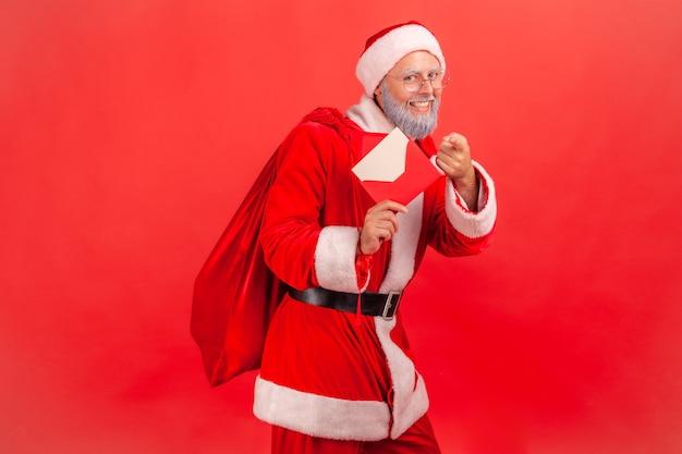 プレゼントを持って物乞いをして立って、おめでとうと手紙を持っているサンタクロース