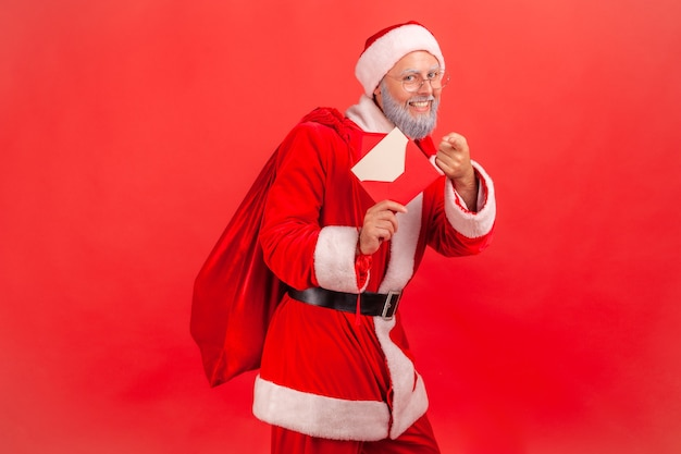 Santa claus standing with beg with presents and holding letter with congratulations