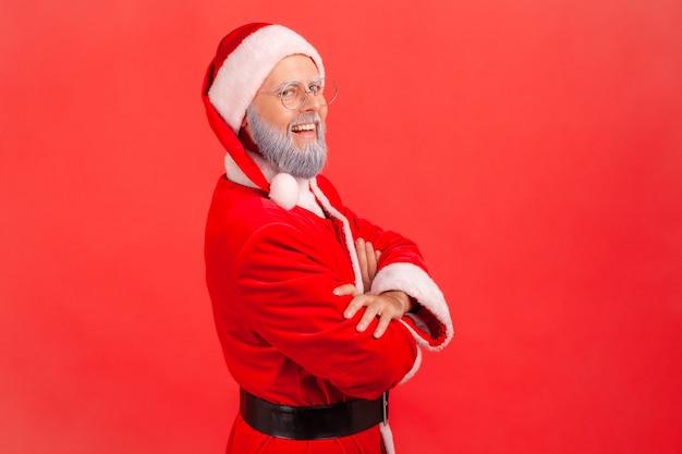 サンタクロースは腕を組んで立って、歯を見せる笑顔でカメラを見ています。