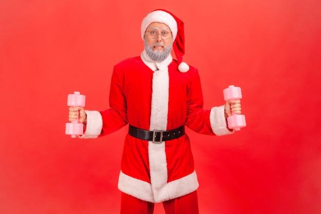 무거운 스포츠 장비를 들어 올리려고 손에 아령을 들고 서 있는 산타 클로스.