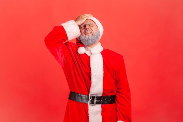안면 손바닥으로 서 있는 산타 클로스는 나쁜 기억 때문에 슬픔을 느끼고 자신을 비난합니다.