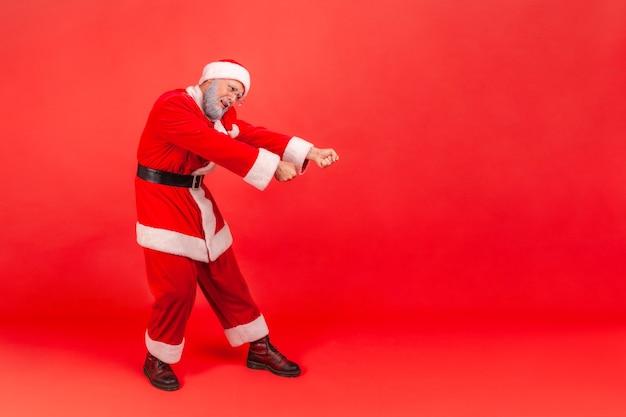 눈에 보이지 않는 밧줄을 당기기 위해 주먹을 들고 서 있거나 몸짓을 당기는 산타클로스.