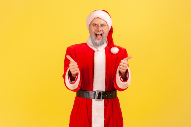 Santa claus standing with open mouth, screaming happily, showing thumb up to camera.