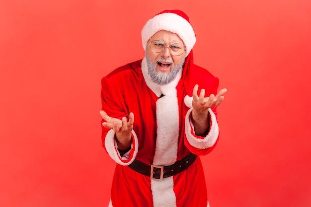 이유를 묻는 분개한 공격적인 얼굴과 손을 들고 서 있는 산타클로스.
