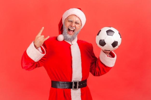 Санта-клаус стоит с футбольным мячом в руках и показывает рок-знак на камеру.