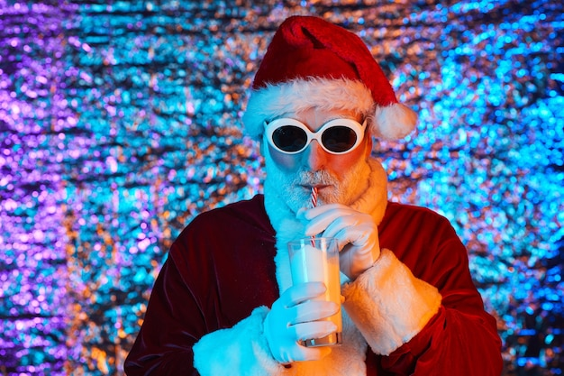 Santa claus in sunglasses holding glass and drinking milk from drinking straw