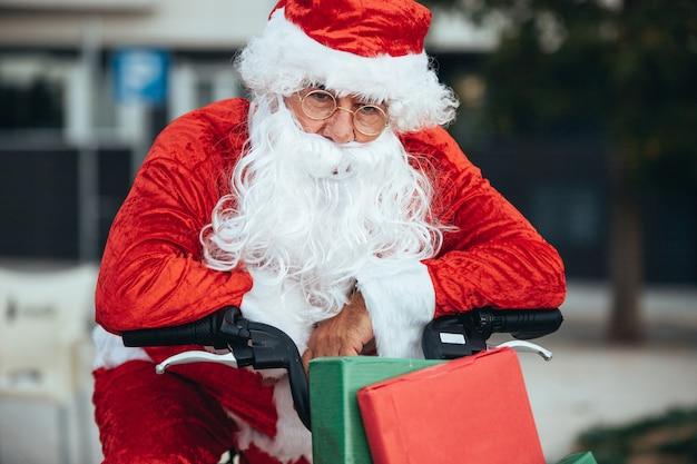 Санта-клаус с изможденным выражением лица поддерживает велосипед, полный подарков. рождественское время