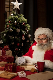 Santa claus surrounded by christmas gifts