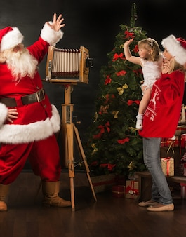 Santa claus taking picture of cheerful woman with little girl