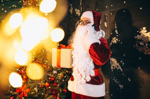 Santa claus talking on the phone and holding a present