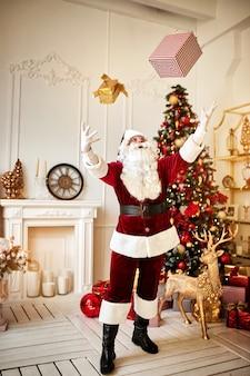 던지고 노는 산타 클로스 선물 벽난로와 크리스마스 트리 근처 선물. 새 해와 메리 크리스마스, 해피 홀리데이 개념