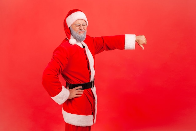Santa claus thumbs down, expressing disapproval, criticizing and disagreeing with suggestion.