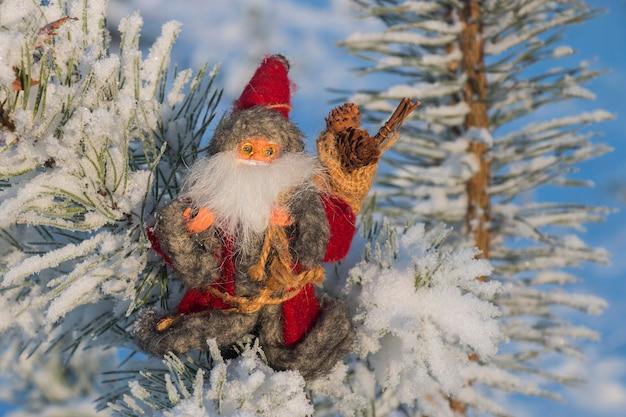 Игрушка деда мороза на заснеженной ветке дерева