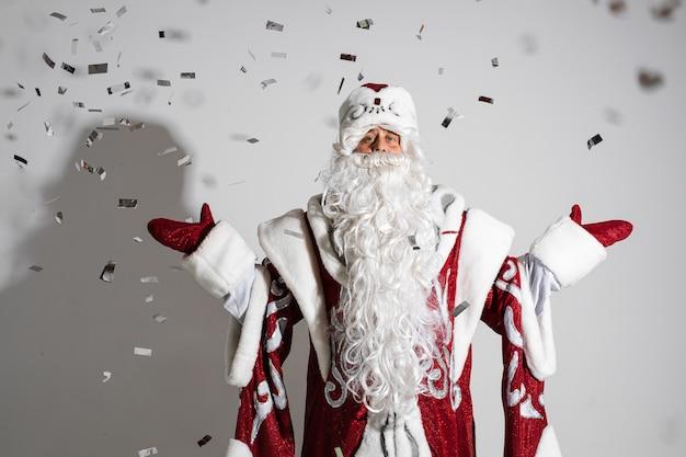 Санта-клаус под праздничным рождественским конфетти показывает приветственный жест