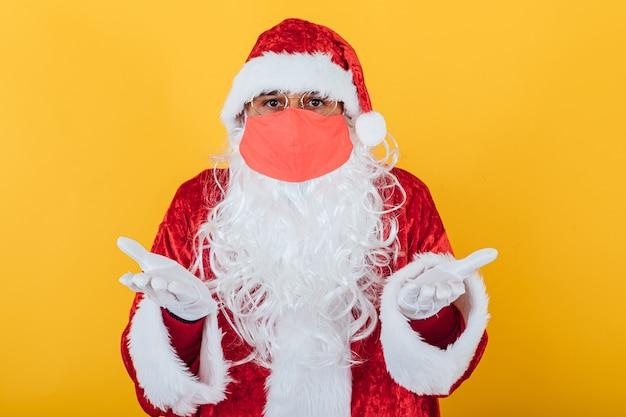 黄色に、辞任のジェスチャーで赤いフェイスマスクを身に着けているサンタクロース