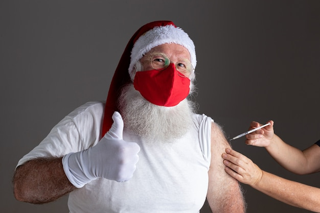 Santa claus wearing face mask getting vaccinated with injection