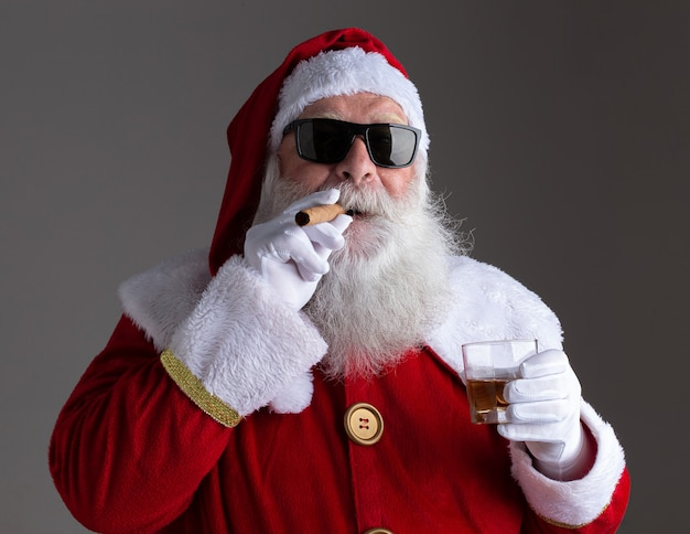Santa claus wearing sunglasses smoking a cigar and drinking whisk on dark background