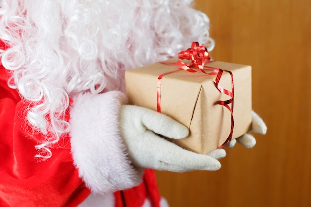 Santa claus in white gloves and white beard holding gift box.