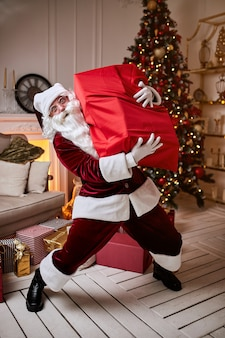 큰 빨간 선물 가방을 든 산타 클로스는 아이들에게 선물을 가져 오기 위해 서두 릅니다. 새 해와 메리 크리스마스, 해피 홀리데이 개념