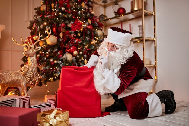 큰 빨간 선물 가방을 든 산타 클로스는 아이들에게 선물을 가져 오기 위해 서두 릅니다.