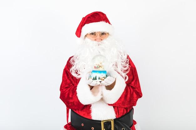 彼女の手に、白い背景の上のクリスマスのスノードームを持つサンタクロース