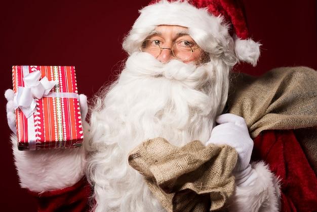 빨간색 배경에 선물 상자 산타 클로스