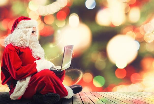 Санта-клаус с ноутбуком и рождественской елкой на фоне