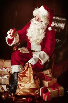 豪華な白ひげ、サンタの帽子、贈り物と一緒に座っている赤い衣装を持つサンタクロース