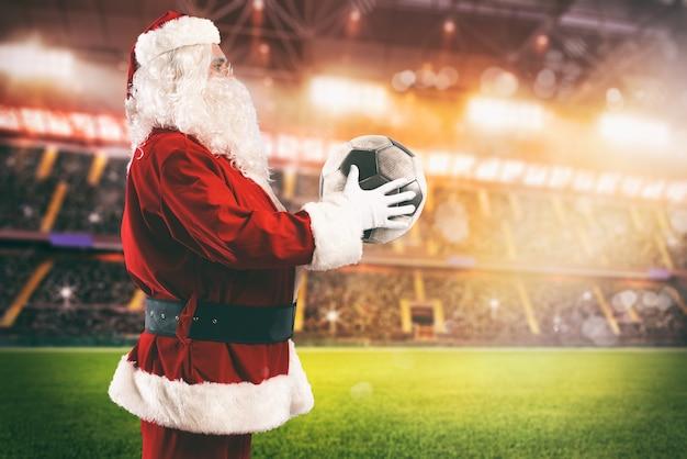 Санта-клаус с футбольным мячом в руках на футбольном стадионе