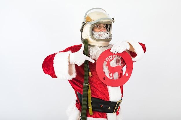 Санта-клаус в шлеме космонавта держит знак движения с оленями на белом фоне