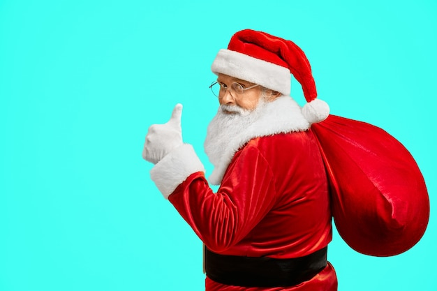 Santa claus with bag showing thumb up.