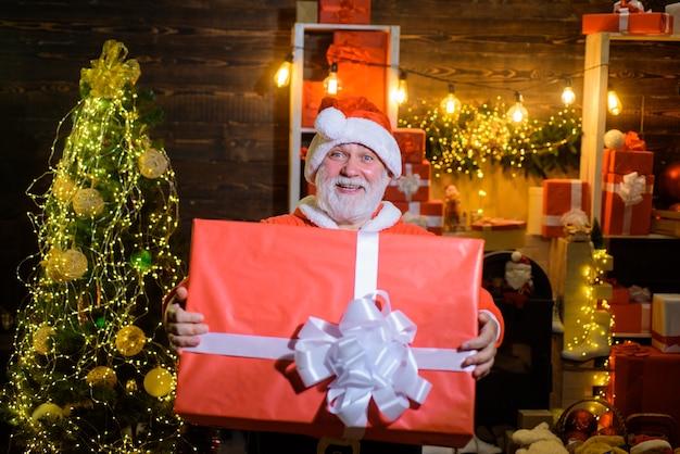 Санта-клаус с большой подарочной коробкой с рождеством и новым годом бородатый мужчина в костюме санта-клауса