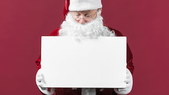 Santa Claus with blank white paper in hands