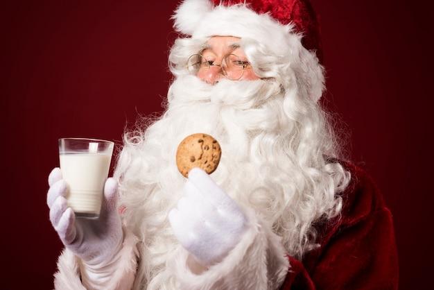 Babbo natale con un biscotto e un bicchiere di latte