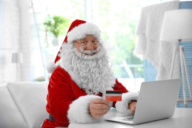 Санта-клаус с кредитной картой и ноутбуком дома